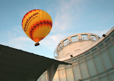 Questacon hot air balloon flying over the Questacon building.