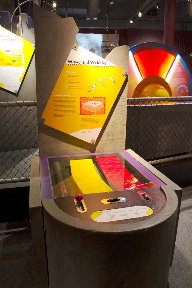A yellow and red series of horizontal rods under a glass display case. The horizontal component of the case has a yellow information panel.