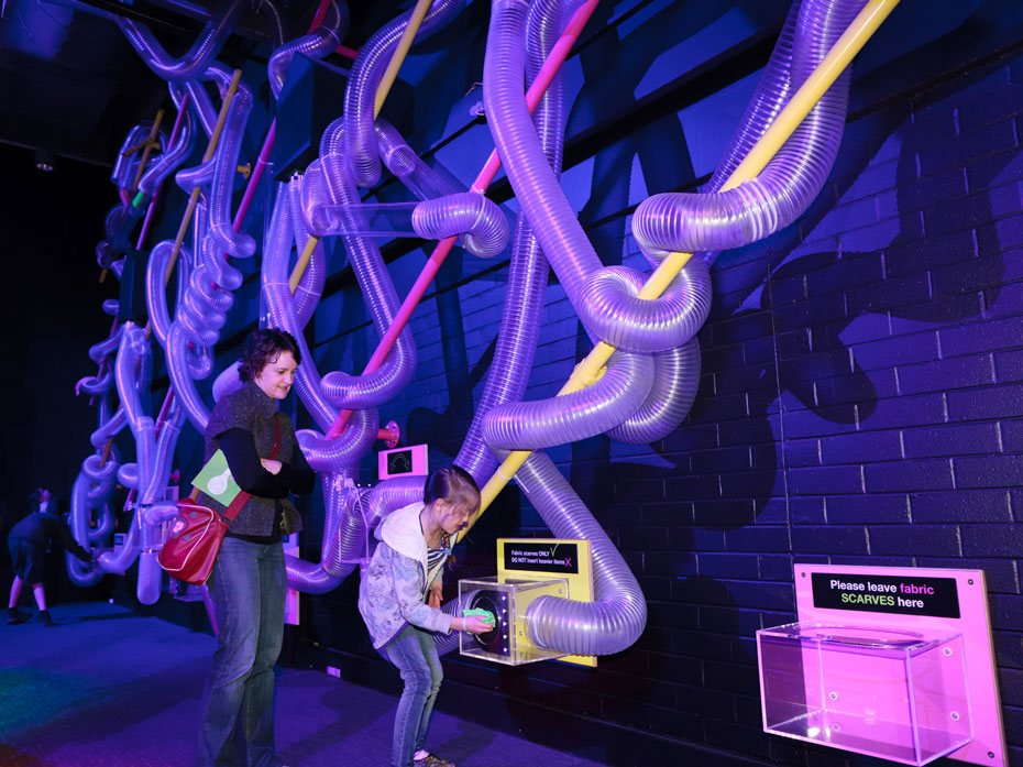 A young girl placing a green scarf in a perspex box that is connect to a series of large air tubes mounted on a purple/blue wall. A woman watches on behind her.