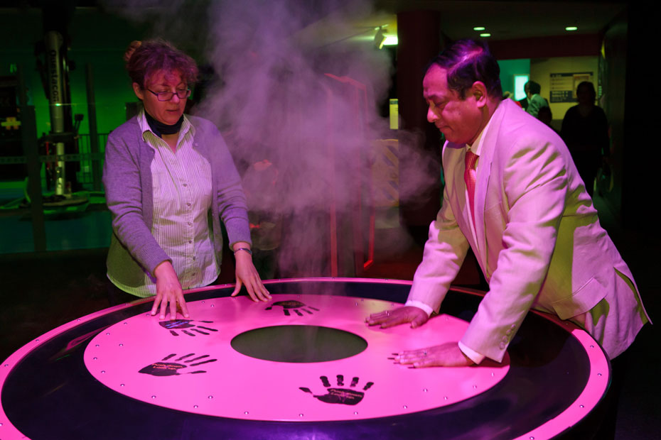 A woman and man pressing down with both sets of hands on a round table. There is smoke rising from the centre of the table, and hand prints painted on the table top surface.