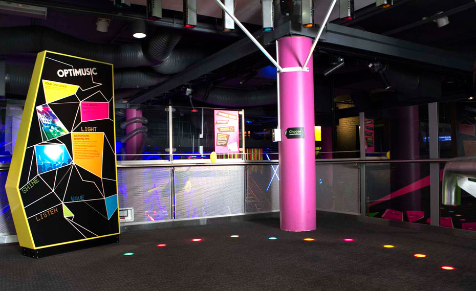 A multi coloured sign with the words 'Optimusic' at the top, along side a carpeted area with a pink structural pole, and different coloured floor lights in a curved line.