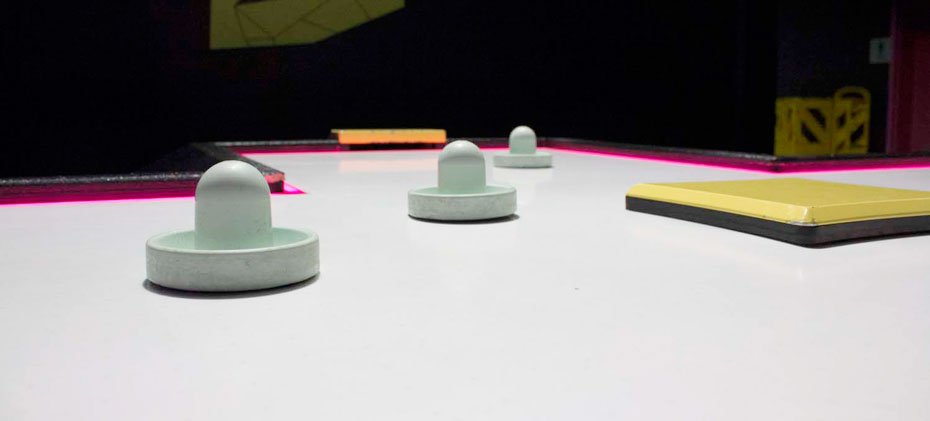 A cross shaped black and yellow air hockey table with a white surface. There are 3 white plastic hitting items on the table top.