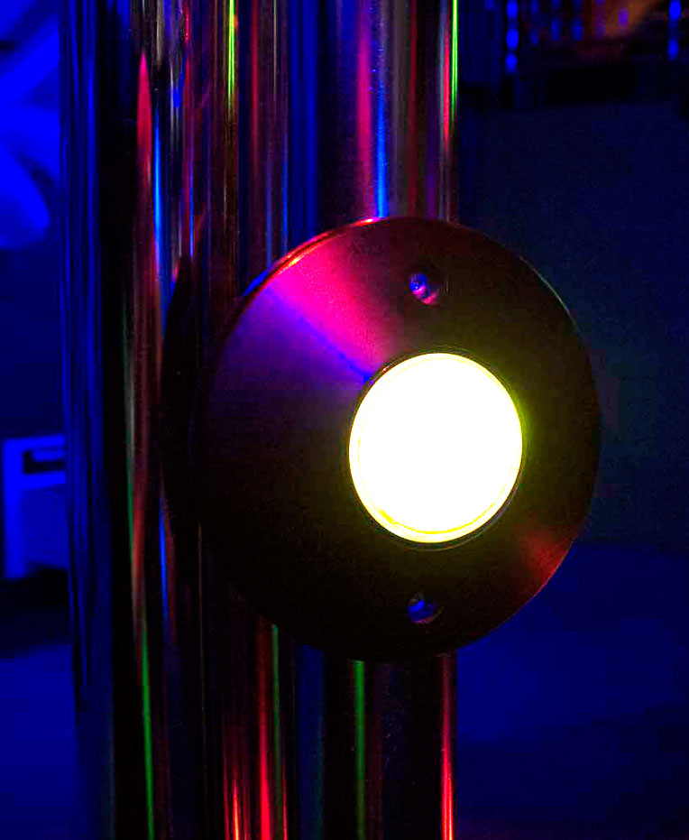 A illuminated button mounted on a stainless steel vertical pole