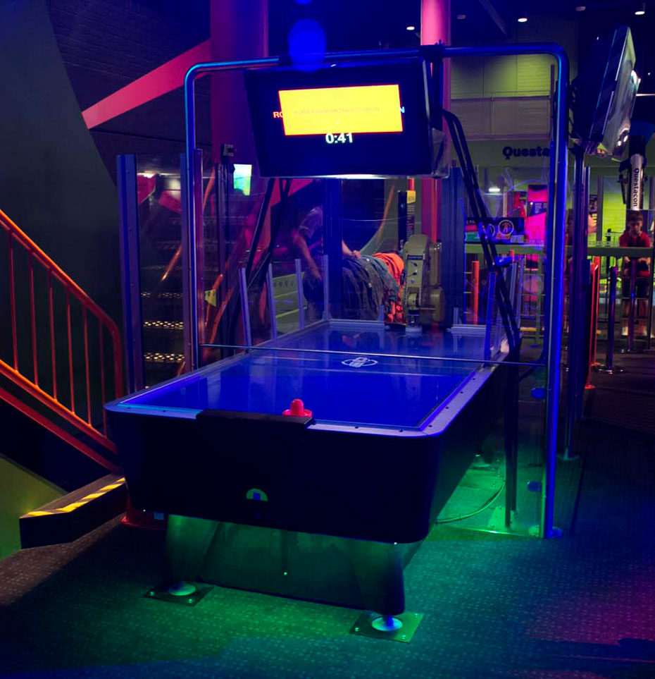 A blue hockey table with a tv screen above it and perspex glass enclosing the a robot arm at the back.