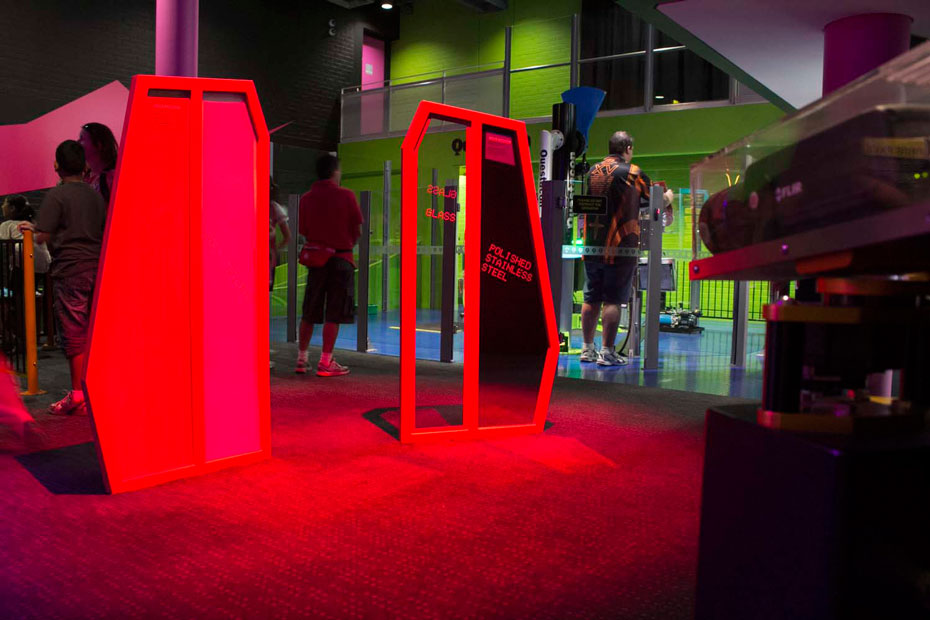 A black thermal camera enclosed in a protective perspex box, pointing at two red upright display boards with people in the background