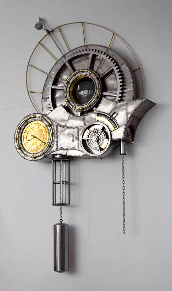A large steel and brass steampunk wall clock sitting on a grey wall