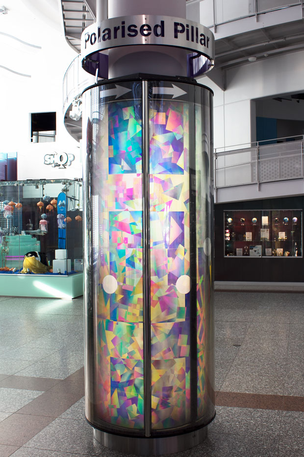 A large pilar display with different geometric shapes, sizes and colours. The pillar sits in a large foyer.