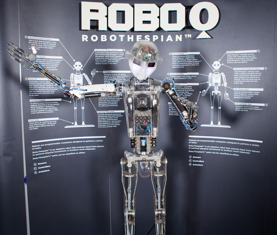A robot with it's arms spread outwards, and a large grey and white information panel behind it with the title 'Robo Q Robothespian'.