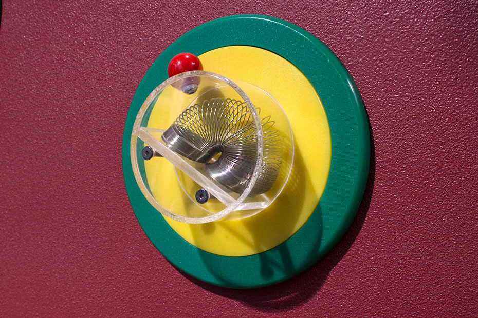 A slinky sitting in a perspex cup attached to a yellow and green disc, attached to a red wall