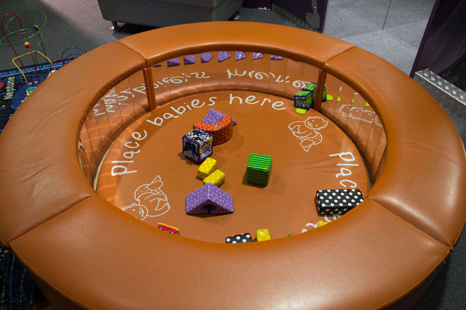 "A round padded tan coloured play area with mirrors in the inside wall and assortment of soft toys in the centre area. The words ""Place babies here"" is written on the padded floor."