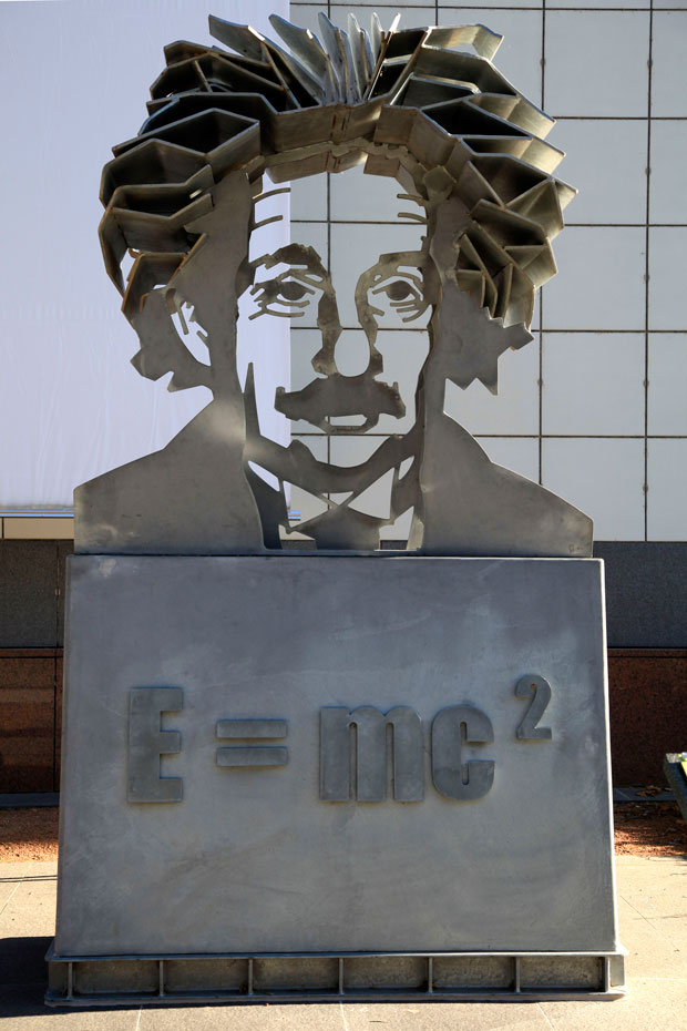 "A metal sculpture of Albert Einstein's head and shoulders sitting on a concrete pillar with the scientific equation ""E = mc squared"" written on the pillar."