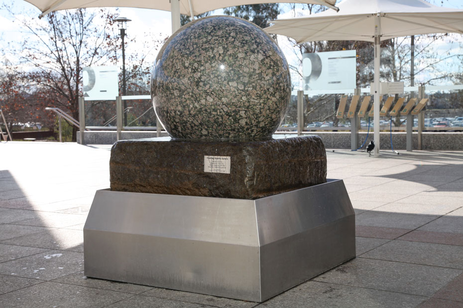 A large granite stone ball sitting on a large slab of stone, which intern sits within a stainless steel bin. Water flows from under the granite and over the stone to the bin.