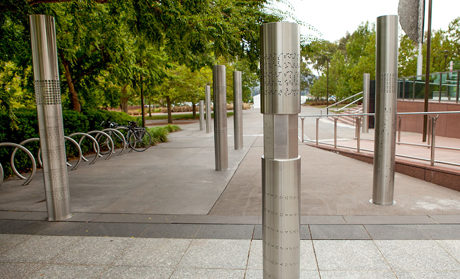 Eight stainless steel vertical poles about 2 metres in height are spaced apart and embedded into a concrete and paved garden area. On each of the poles are laser cut out cryptographic symbols.