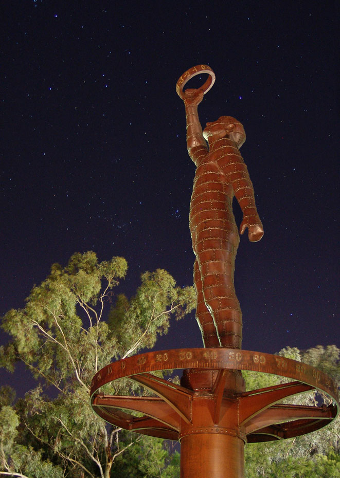 A night time photo of a rusted metal sculpture of a man holding a ring up to the sky with one outstretched arm. There are gum trees lit up in the background and the sky is black with thousands of stars visible.