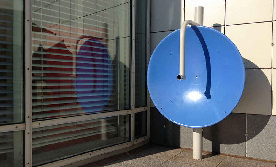A large blue concave vertical dish sits in the corner with a large window to the left and a white wall to the right.