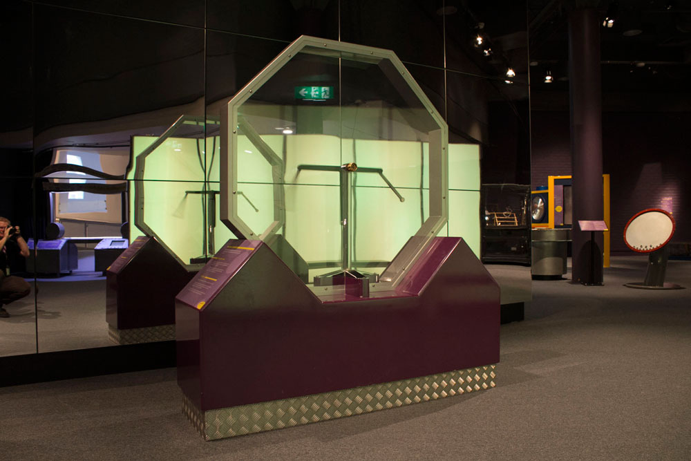 A large octagonal perspex case, with mechanical arms inside, and sitting on a black display base
