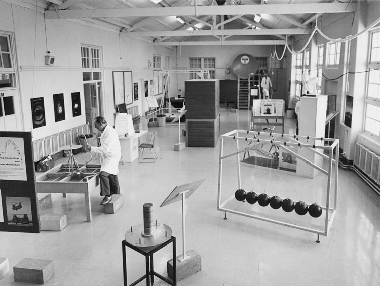 A black and white photo of a white long room with windows on the right and lots of scientific exhibits on the floor.