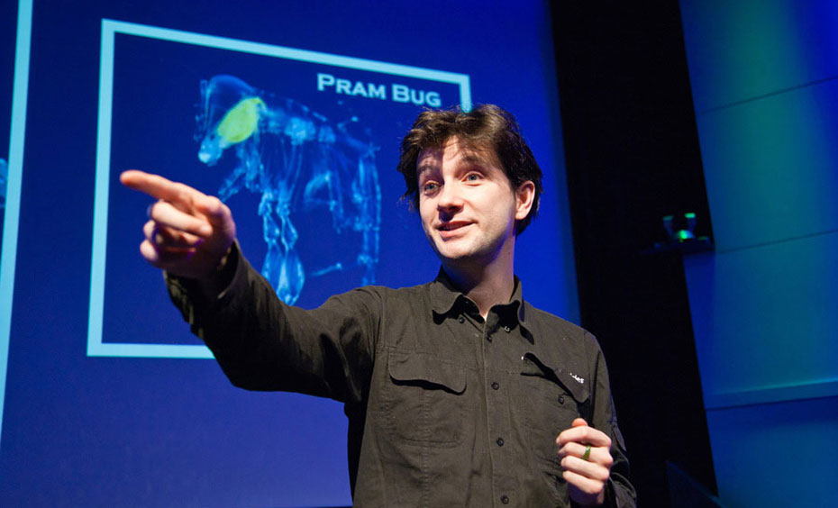A man wearing a collared shirt is pointing and sanding in front of a screen that has a blueprint of a bug on it.