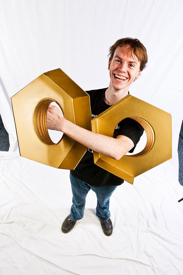 A man smiling and holding two over sized model hex nuts through his left arm.