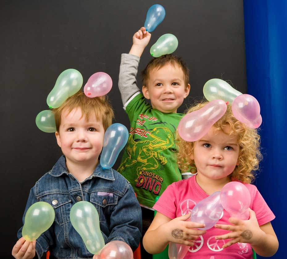 A young boys with balloons clinging to his hair.