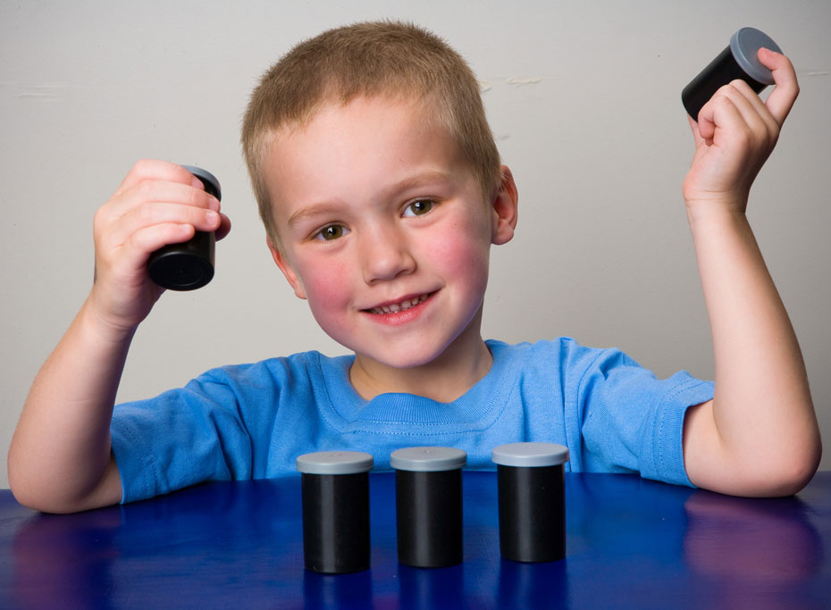 a young boy hold up small plastic film containers