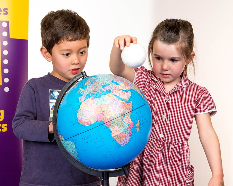 two children looking at a globe