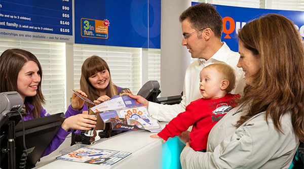 Two young women are standing behind a counter and handing information brochure to a man and woman. The woman is holding a baby. All are smiling.