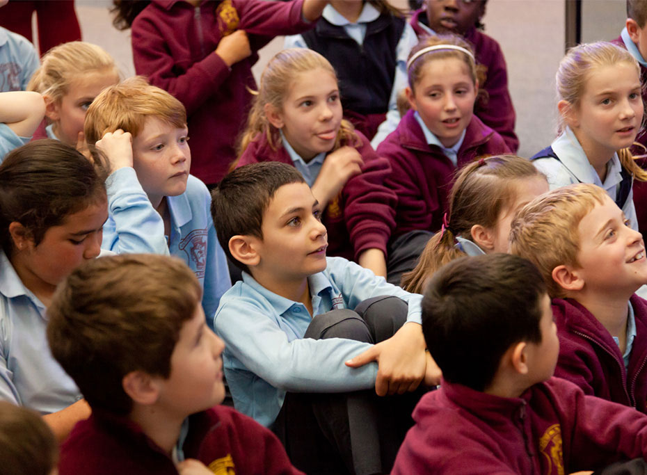 A group of sitting primary school students are looking to right of screen with mixed reactions on their faces.