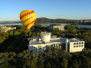 a hot air ballon over a large building surround by trees