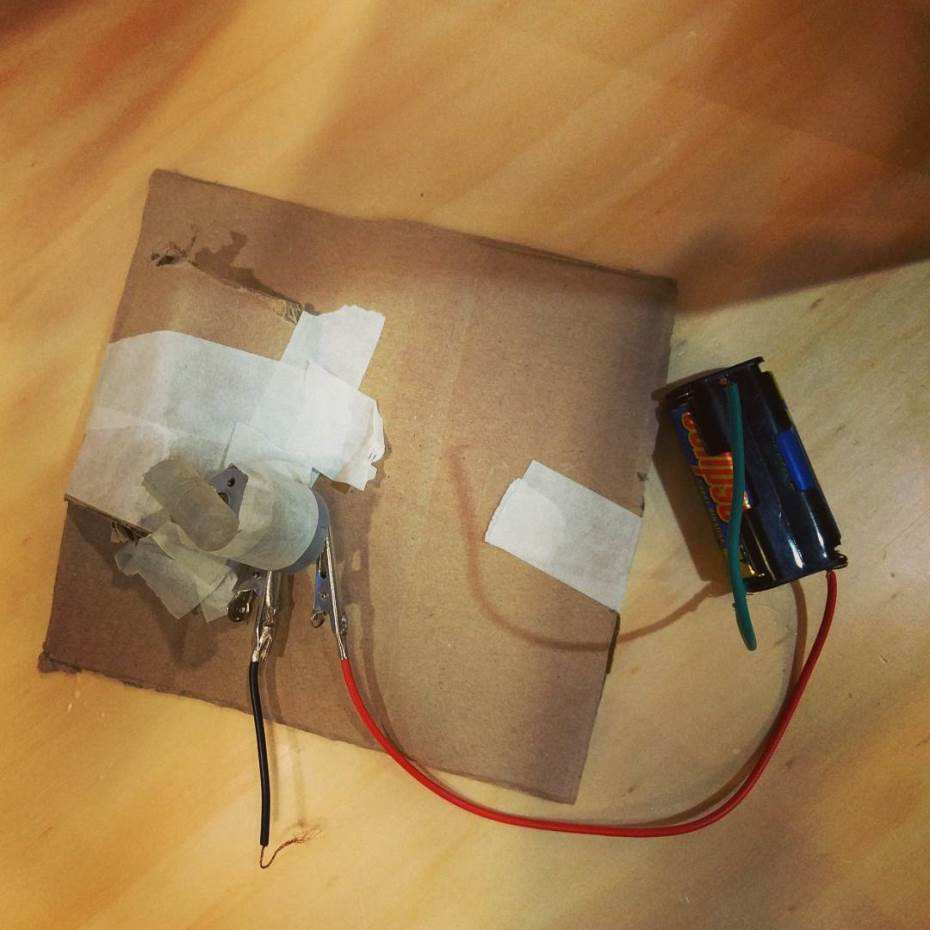 A circuit of a motor and battery taped onto a piece of cardboard