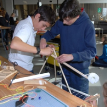 Three students use hot glue, string and wood to construct a solution to the class challenge