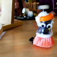 A scrubbing brush with googly eyes and motor moves across a table
