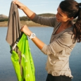 A traveller in the wilderness puts clothes into the Scrubba wash bag