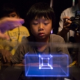 A young boy stares in awe at a 3D hologram produced by VoxieBox