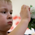 A young boy touching a white rose that is in a vase with blue water.