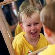 A young boy looking at his reflection and laughing.