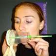 A woman with her mouth resting on a clear plastic cup. The cup as a green straw running through the length of it, with a latex glove over the cup mouth.