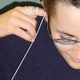 A woman wearing glasses looking down, with her right index finger held to her ear, and white string rapped around her fingers drops downtowards the ground.