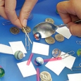A close of two hands holding a spoon and paper clip each, and trying to pick up small square pieces of paper, marbles, segments of drinking straws and 5 cent coins off a blue surface.