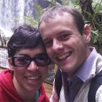 A man and woman smiling in front of a waterfall.
