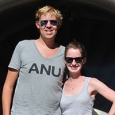 A man and woman standing beside one another and both wearing dark sunglasses.