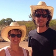 A man and woman both wearing white hats and wearing sunglasses.