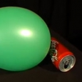 An inflated green balloon next to a Coke can.