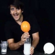 A man holding an orange balloon over a soft drink bottle half filled with white liquid.