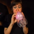 A woman blowing into a pink balloon which itself is inside a plastic soft drink bottle.
