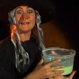 A witch holding a tub of green slime.