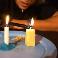 Two candles sitting on a white plate.