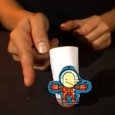 Two hands tapping a white vertical cylinder with a round base, and a cartoon cut out stuck on front.