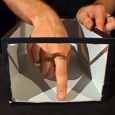 A hand inside a black and white box with the end cut out, is point down.