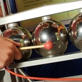 Three chrome spheres sitting in a grey frame, with the centre sphere being struck by a small mallet.